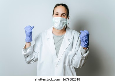 Female doctor with face mask making victory gesture