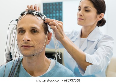 Female doctor fixing electrodes on head of patient