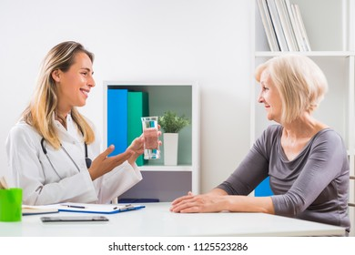 Female doctor is giving advice how is important to drink a lot of water  to her senior woman patient .