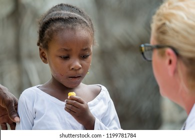 Female doctor giving a food to little black African girl in Africa. Real people