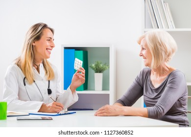 Female doctor is giving  pills to her senior patient for her  health problems.