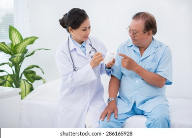 Female doctor giving pills to her senior patient