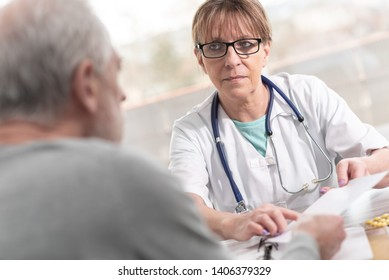 Female doctor giving prescription to her patient in medical office