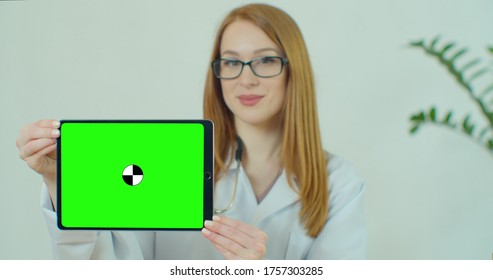 Female Doctor in glasses demonstrating digital tablet with chroma key in hospital, Portrait of woman in white gown with stethoscope in medical office showing digital tablet with green screen.