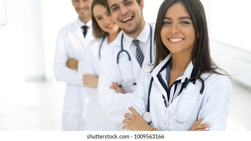 female doctor with group of happy successful colleagues