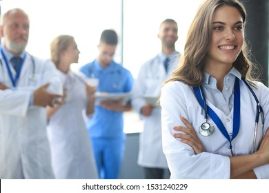 Female doctor with group of happy successful colleagues.