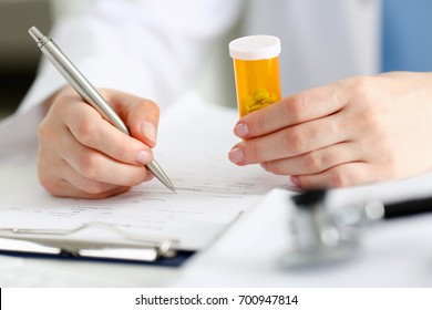 Female doctor hand hold jar of pills and write prescription at worktable. Panacea and life save, prescribe antidepressant, legal drug store, ward round, give or take potion, vitamin aid concept
