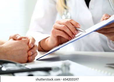 Female doctor hand hold silver pen and showing pad. Physical agreement form signature, disease prevention, ward round reception, consent contract sign, prescribe remedy, healthy lifestyle concept