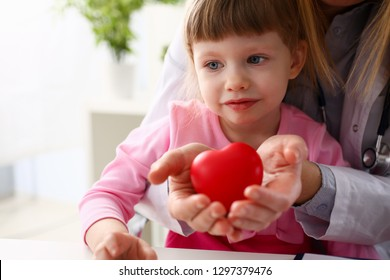 Female doctor and happy little child hold in arms red toy heart closeup. Cardio therapeutist student education CPR 911 life save physician make cardiac physical pulse rate measure arrhythmia lifestyle
