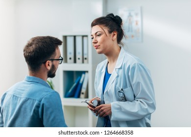 Female Doctor in her Medical Office with Stethoscope talking to Patient