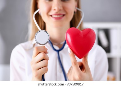 Female doctor hold in arms red toy heart and phonendoscope head closeup. Cardio therapeutist, student education, CPR, 911 life save, physician make cardiac physical, pulse rate measure, arrhythmia