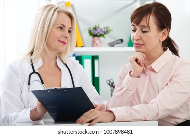 Female doctor holding application form while consulting patient. Selective focus.