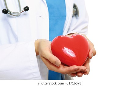 A female doctor holding a heart, close-up, isolated on white background