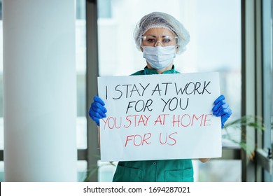 Female doctor holding placard with 'I stay at work for you, you stay at home for us' message during coronavirus pandemic.