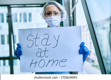 Female doctor holding placard with stay at home text as appeal during COVID-19 epidemic.