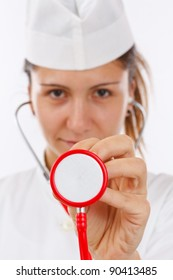 Female doctor holding stethoscope pointed toward camera (selective focus)