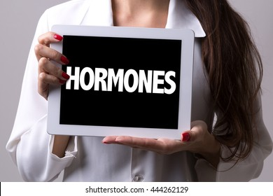 Female doctor holding a tablet with the text: Hormones