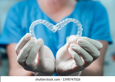 Female doctor holding two transparent heart-shaped dental aligners
