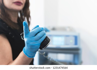 Female doctor holding ultrasound lipolysis instrument in hand. Space for text.