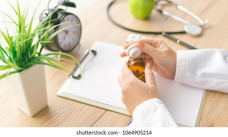 Female doctor holding unlabeled bottle of various pills and medication, generic drugs concept, prescription medicine and healthcare
