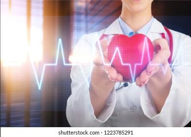 Female doctor holds red heart