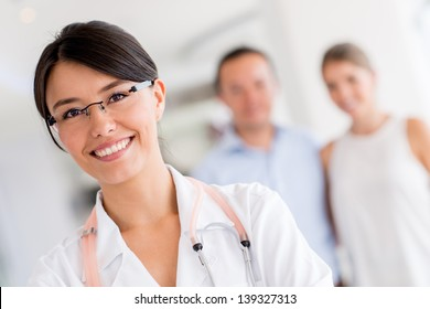 Female doctor at the hospital with patients at the background