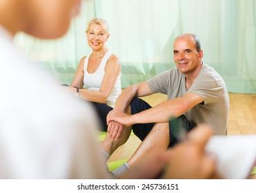 Female doctor keeping eye at smiling senior spouses during training. Focus on man