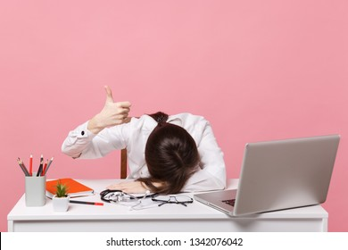 Female doctor laid her head down on desk, work on computer, medical document in hospital isolated on pastel pink background. Woman in medical gown glasses stethoscope. Healthcare medicine concept