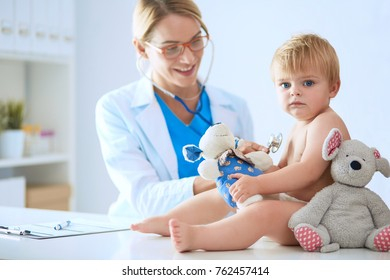 Female doctor is listening kid with a stethoscope in clinic