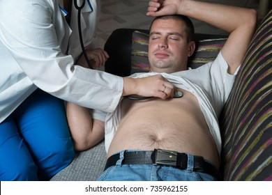 A female doctor listens to the patient's chest in his home.