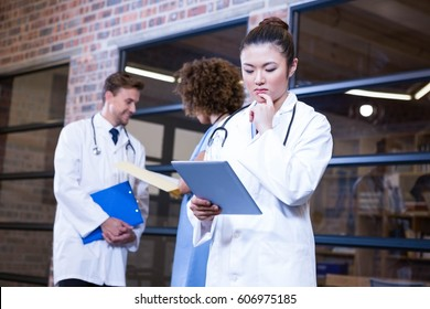 Female doctor looking at digital tablet near library and colleagues standing behind and discussing