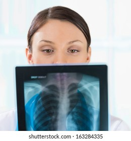 Female doctor looking at a lungs or torso xray, fluorography