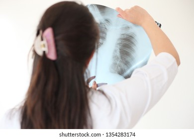 Female doctor looking at an x-ray in a hospital - Image
