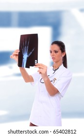 Female doctor looking at an x-ray  in light medical environment looking at an xray