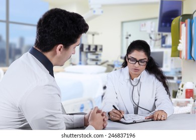Female doctor make a prescription for her patient after consulting in the hospital