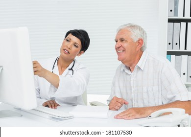 Female doctor with male patient reading reports on computer at medical office