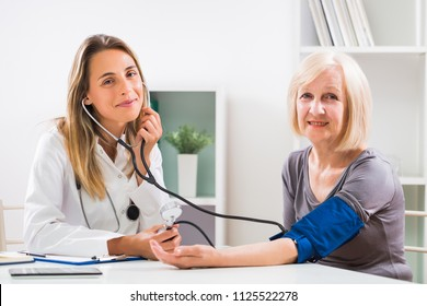 Female doctor is measuring blood pressure to her senior patient in doctor's office.