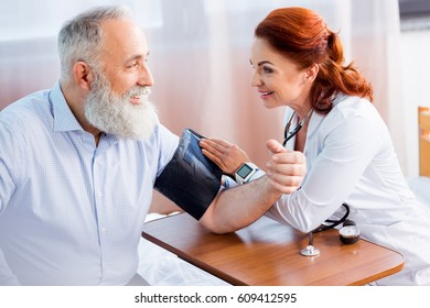 Female doctor measuring pressure of smiling senior male patient