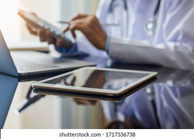 Female doctor with medical stethoscope or pharmacist using calculator and work on laptop computer with digital table on the desk at clinic or hospital. Medical healthcare costs and financial concept.