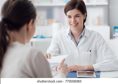 Female doctor meeting with a patient in the office, she is giving a prescription to the woman, healthcare and medicine concept