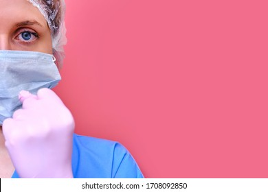 Female doctor menacingly shows a fist on a pink background, copy space for text. Girl nurse in a medical mask, concept of resistance to the coronavirus epidemic. Stay home