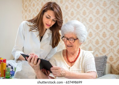 Female doctor or nurse discussing reports with senior patient. Home care concept.
