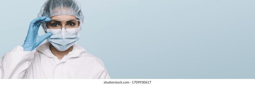 Weibliche Ärztin oder Krankenschwester Tragen latexschützende Handschuhe und medizinische Schutzmaske und Brille auf dem Gesicht. Schutz für Coronavirus COVID-19, mit Kopienraum für Ihren individuellen Text.