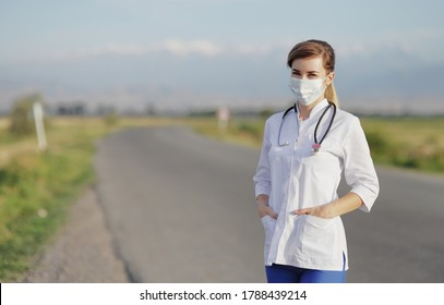 Female doctor or nurse wearing a protective face mask next to a rural road.
