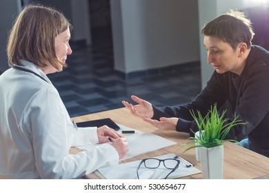 Female doctor and patient consultation during medical exam in hospital examination room