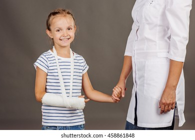 female doctor pediatrician holds the hand of a  small girl patient . image on gray background. medicine, health care and people concept