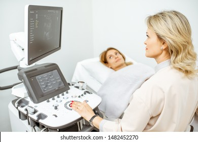 Female doctor performs ultrasound examination of a women's pelvic organs or diagnosing early pregnancy at the medical office