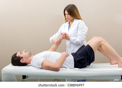 Female doctor physiotherapist practicing massage to her arm male patient in medical center