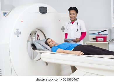 Female Doctor Preparing Patient For CT Scan In Hospital