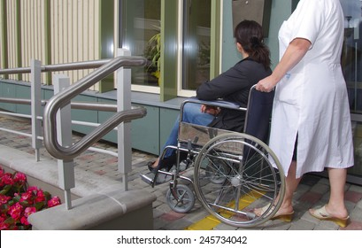 Female doctor pushing an patient in wheelchair.
